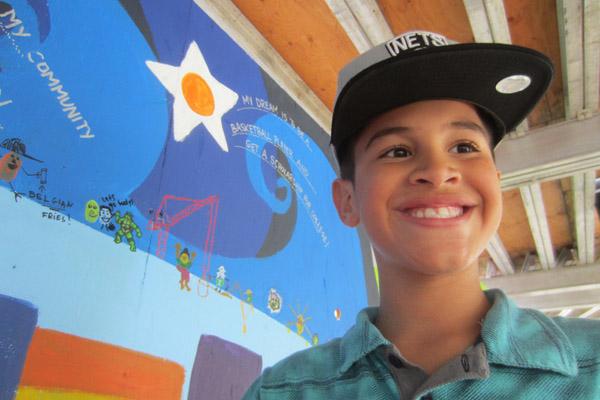 Johanny standing before a Community Art Center mural on Massachusetts Avenue