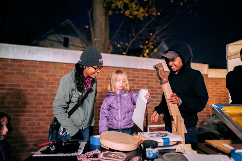 A little girl looks at the print that's come from the torilla press in front of her, while 2 young adults look on, smiling. Image by Faizal Westcott, courtesy of Urbano Project.