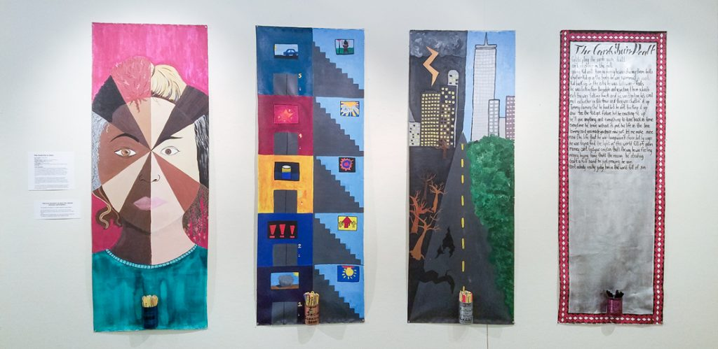 Four panels hanging on a gallery wall.