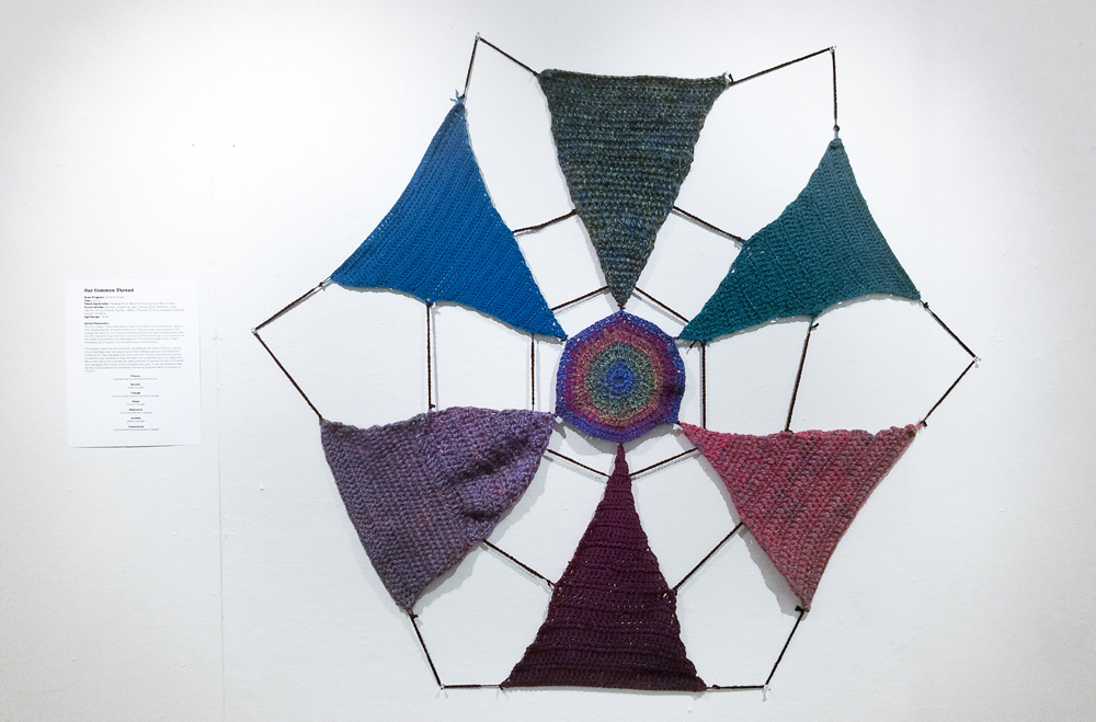 A wall hanging of a multi-colored, crocheted hexagon