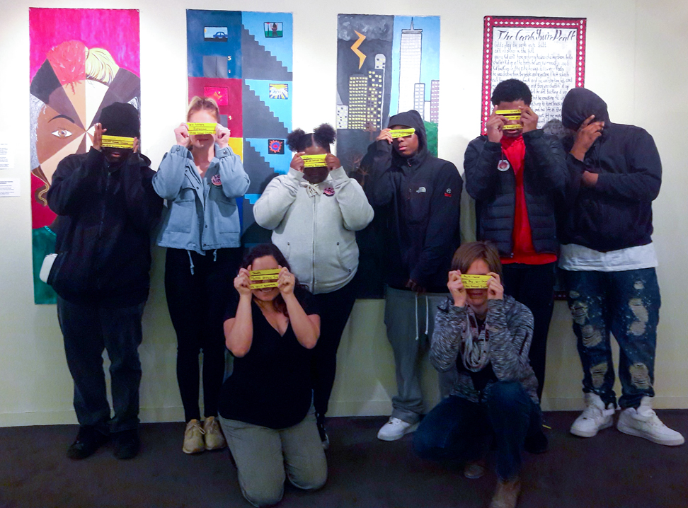 Youth artists standing in front of their installation, their faces obscured with yellow masks.