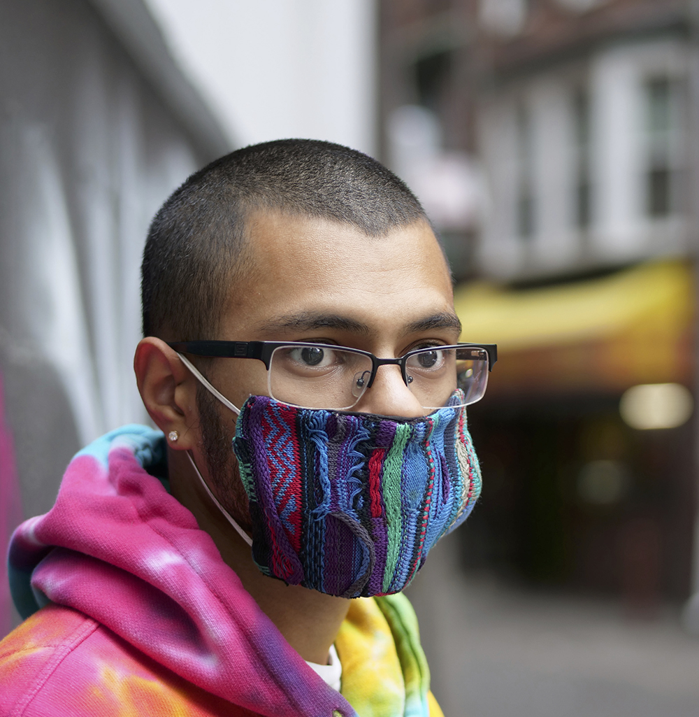 Young man with a buzz cut, glasses, a colorful face mask,wearing a tie-dyed hoodie