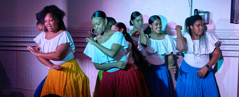 a group of women perform Afro Cuban dance