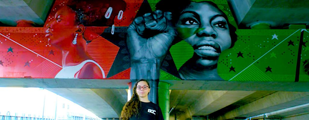 Young woman with long hair and glasses stands in front of a colorful mural with images of black women activists painted on an overpass