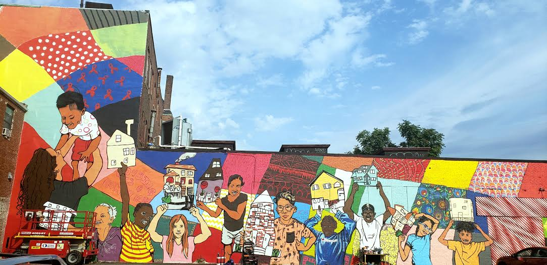 a brightly colored mural depicting young people of different backgrounds holding different kinds of houses (single-family, apartment building). It covers the side of a building. A blue sky above it.